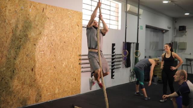 uomo che si arrampica su una corda - inerpicarsi video stock e b–roll