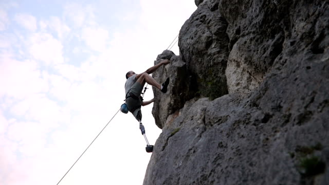 Man climbing high One man, disability young man with prosthetic leg, free climbing on a rocky mountain in nature. prosthetic equipment stock videos & royalty-free footage