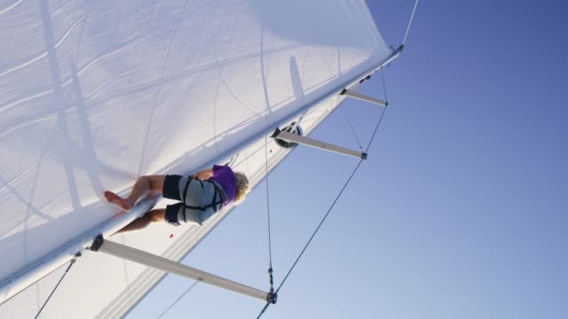 Man climbing mast on sunny sailboat, real time Man climbing mast on sunny sailboat. MS, tilt up, real time.Shoot in 8K resolution mast sailing stock videos & royalty-free footage