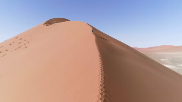 Man climbing on a huge dune. Aerial view