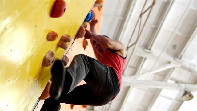 mann auf praxis wand klettern - bouldering stock-videos und b-roll-filmmaterial