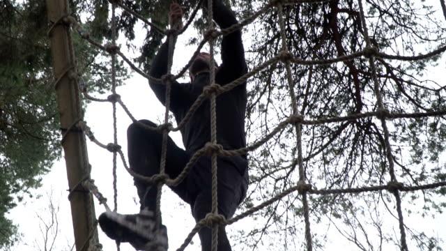 mann klettert gepäcknetz auf assault course / hindernis-parcours - netzgewebe stock-videos und b-roll-filmmaterial