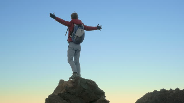 A man climbs a mountain peak and raises his hands triumphantly to the sky
