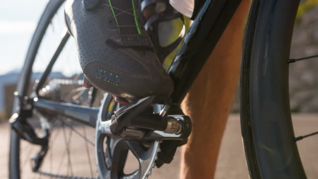 man clipping in cycling shoes in to road bike pedal - ciclismo su strada video stock e b–roll