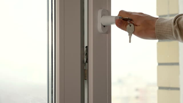 A man closing a window with a key A man closing a window with a key handle stock videos & royalty-free footage