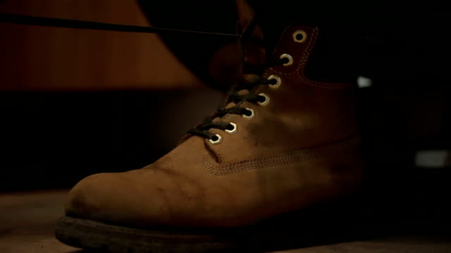 man clothes and tying his shoes video