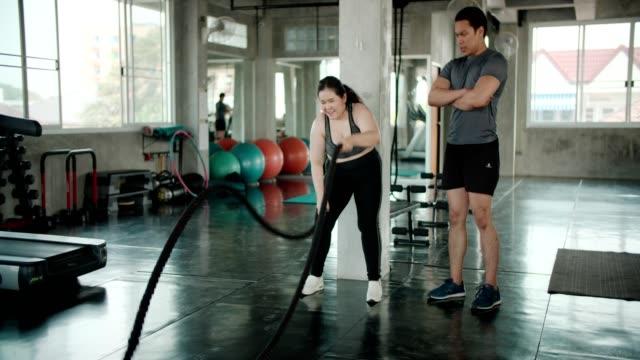 vídeos de stock e filmes b-roll de man coaching asian woman on ropes gym exercise - agachar se
