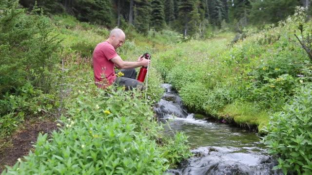남자는 하이킹 물 수집 - 한 명의 중년 남자만 스톡 비디오 및 b-롤 화면
