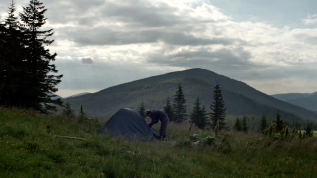 A man comes out of the tent installed in the reserve outdoors among the trees video