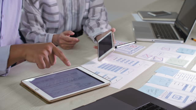 man comparing charts on two gadgets - paragone video stock e b–roll