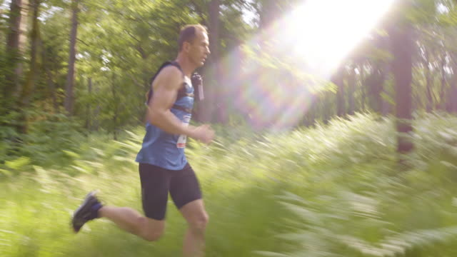 TS Man competing in a trail run through the forest video