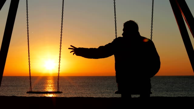 Man complaining alone missing his partner Back view silhouette of a sad man complaining alone missing his partner siting on swing at sunrise relationship breakup stock videos & royalty-free footage