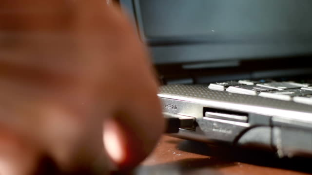 A man connect a USB flash drive to a laptop. Video with volumetric light video