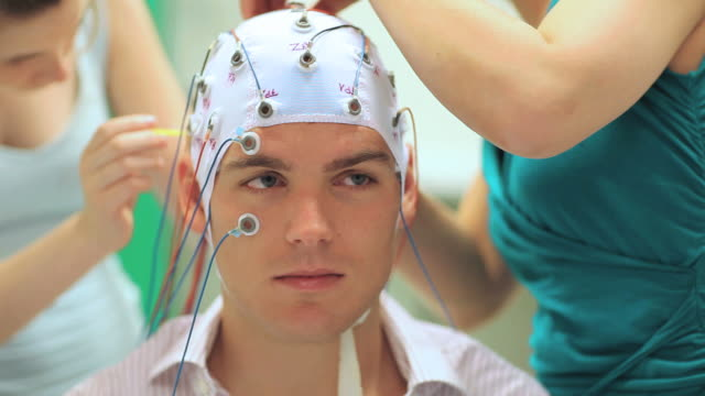 man connected with cables to computer - EEG for resarch for a scientific experiment, two woman prepare a young man with cables to a computer, EEG for research electrode stock videos & royalty-free footage
