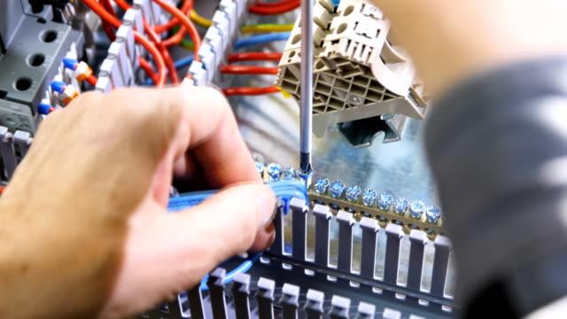 vídeos de stock, filmes e b-roll de homem conecta fios na placa de interruptor com parafuso - eletricista