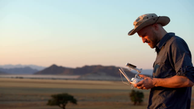 mann controlling drohne. - afrikanische steppe dürre stock-videos und b-roll-filmmaterial