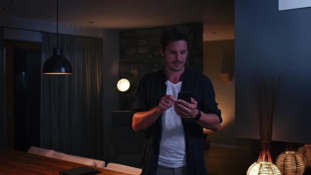 uomo che controlla le luci attraverso il cellulare a casa - illuminato video stock e b–roll
