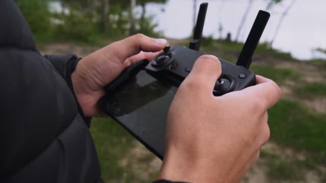 人間は、リモコン、クローズアップを使用してドローンを制御します。湖の近くの自然の中で男。ドローンを制御する男。 - コントロール点の映像素材/bロール