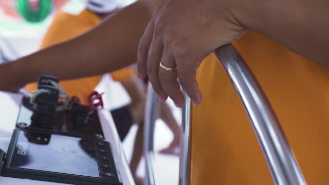 mężczyzna steruje kierownicą jachtu podróżującego po oceanie - ster fragment pojazdu filmów i materiałów b-roll