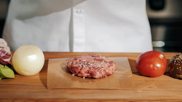 Man cooking chief in white robe drips coarse salt on uncooked meat video