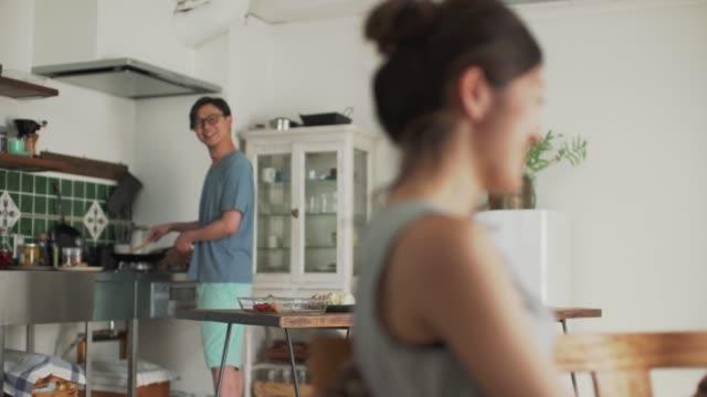 vidéos et rushes de un homme cuisinant dans la cuisine et une femme retenant une conversation numérique de tablette avec un sourire - seulement des japonais