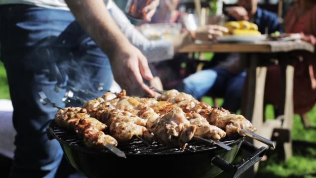 man cooking meat on barbecue grill at summer party video