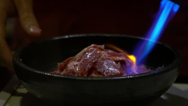 vídeos de stock e filmes b-roll de man cooking with fire blowtorch a fresh meat in bowl at japanese restaurant - burned cooking