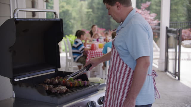 man cooking with grill at backyard barbeque - alla griglia video stock e b–roll
