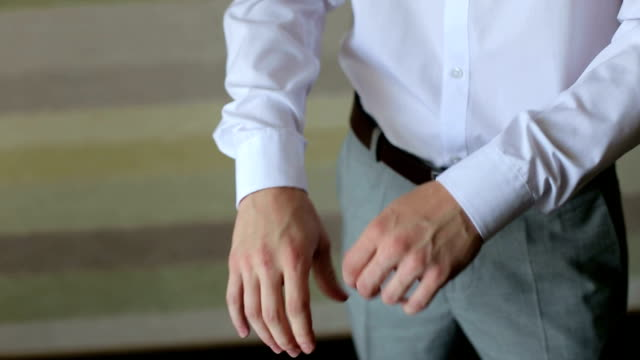 Man correct sleeves on shirt, hands close-up. Groom, man correct sleeves on shirt, hands close-up, dressing, man's style. Sexy man buttons cuff-link on cuffs sleeves luxury white shirt. human joint stock videos & royalty-free footage
