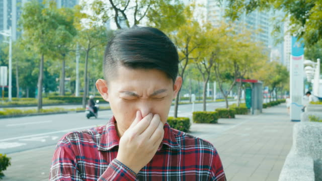 man coughing and sneezing outdoors in the city video