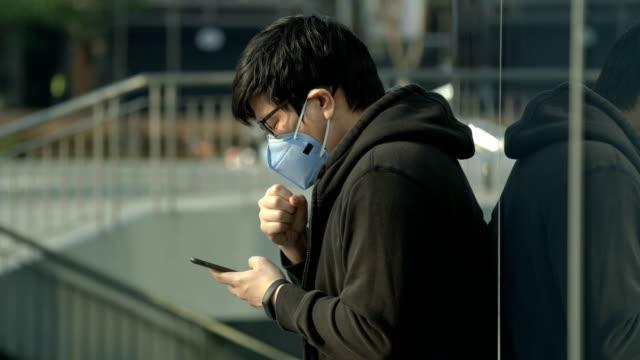 stockvideo's en b-roll-footage met man hoesten tijdens het spelen van telefoon in de stad met luchtvervuiling - mirror mask