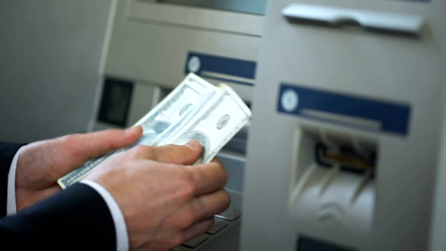 Man counting dollars withdrawn from ATM, putting cash in wallet, 24h service video