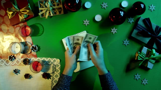 Man counting his money over notepad with expenses writings by New Year table with chroma key, top down shot video