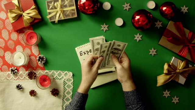 Man counting his money over notepad with expenses writings by Christmas table with chroma key, top down shot video