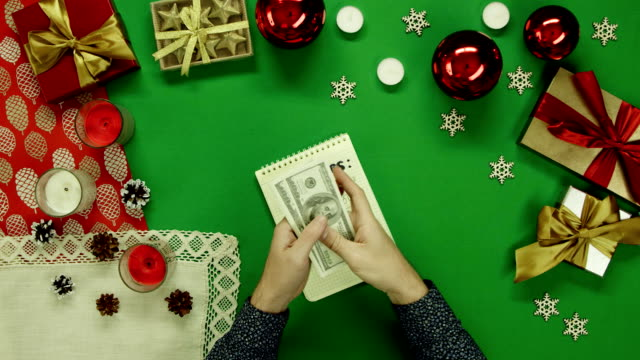 Man counting his money over notepad with expenses writings by Xmas table with chroma key, top down shot video