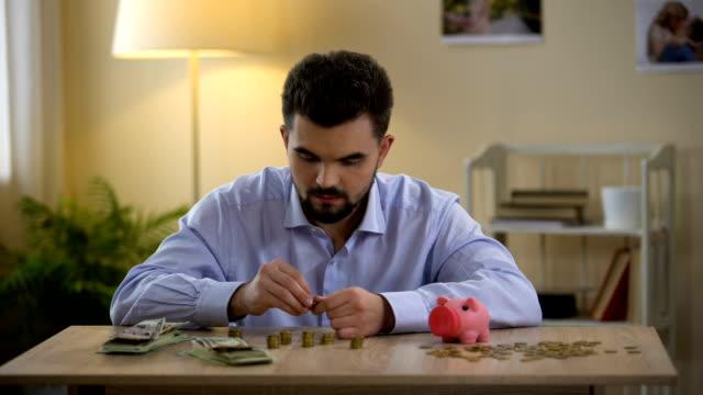 man räknar pengar och sätta myntet i spargris, finansiell kompetens, budget - stavning bildbanksvideor och videomaterial från bakom kulisserna
