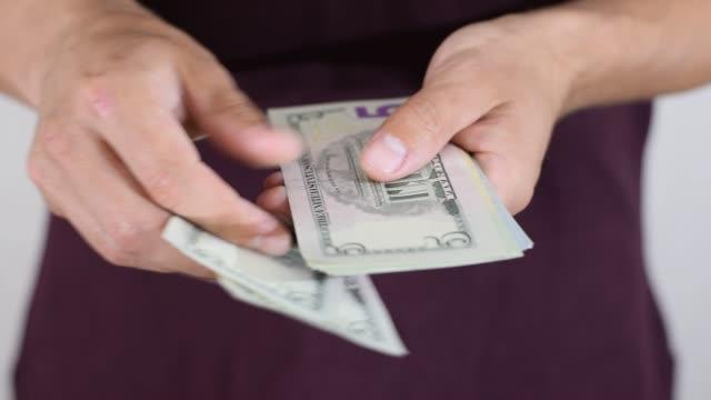 vídeos de stock, filmes e b-roll de homem conta cinco notas de dólar em um pacote. notas do dólar de denominações diferentes. - bico