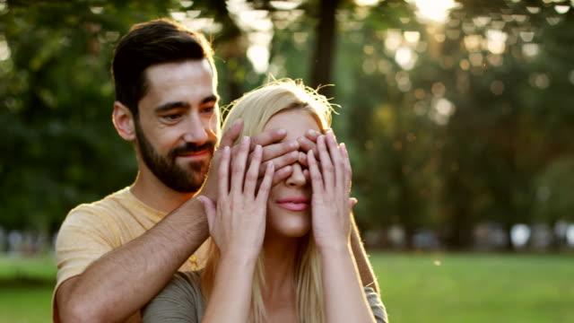 man covering eyes to his girlfriend - kołdra filmów i materiałów b-roll
