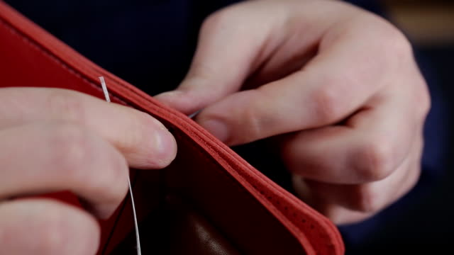 man creates a brown leather wallet with his own hands with a needle in the leather workshop, closeup - tailor working video stock e b–roll