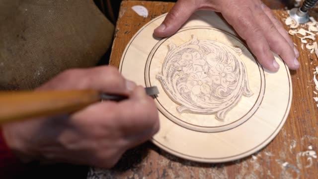 man creating decorative wood plate - incisione oggetto creato dall'uomo video stock e b–roll