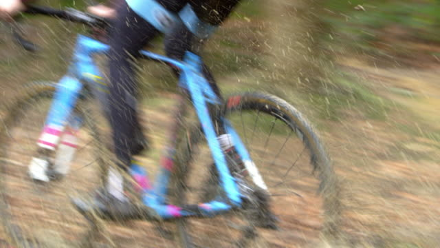 Man cross-country cycling  splashes through a puddle, shot on R3D video