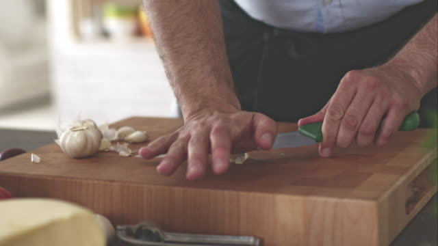 Man crushing and squeezing garlic, close-up video