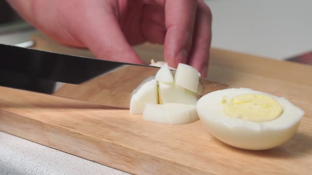 man cuts a boiled eggs into circles with a large knife on a kitchen board in the kitchen at home. home cooking salad ingredient - варёный стоковые видео и кадры b-roll