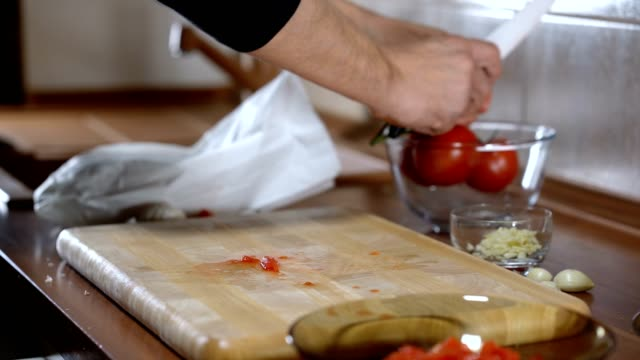 man cuts a tomato for cooking bruschetta video