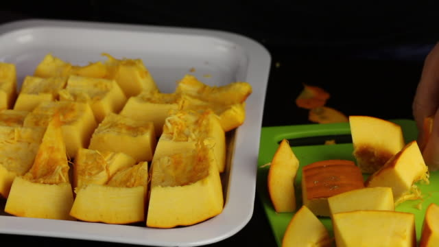 a man cuts an orange pumpkin into pieces. pieces stacks on a tray. world vegan day. - manica video stock e b–roll