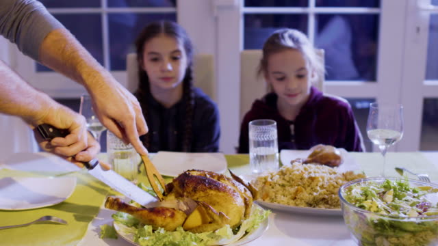 Man cuts chicken at the festive table and put chicken thigh on daughter's plate video