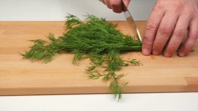 a man cuts dill with a japanese knife santoku, hands, close-up - articoli casalinghi video stock e b–roll