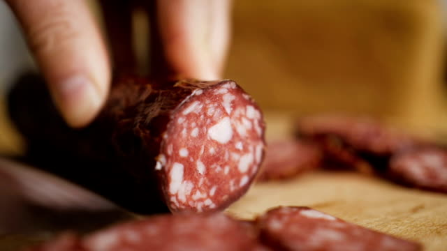 man cuts into thin slices fatty sausage. shooting closeup. chef cutting salami with a knife on a wood board close up. - italian food stock videos & royalty-free footage