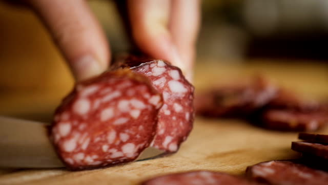 man cuts into thin slices fatty sausage. shooting closeup. chef cutting salami with a knife on a wood board close up. - cucina italiana video stock e b–roll