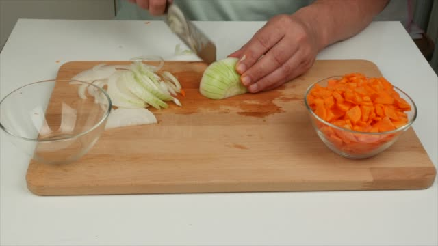 a man cuts onions with a japanese knife nakiri onions on a wooden board - alliacee video stock e b–roll